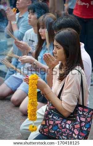 BANGKOK, THAILAND -Â?Â? DECEMBER 29 2013: Thai people pray before New Year at the shrine of the four-faced Brahma (Phra Phrom) on December 29, 2013 at Erawan, Bangkok, Thailand.  - stock photo