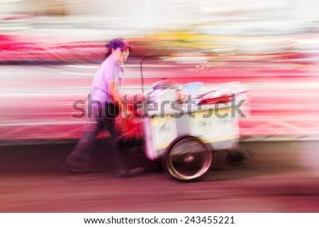 BANGKOK, THAILAND - DECEMBER 16, 2014: Thai woman with a mobile cook shop on a handcart, shown in creative motion blur. Bangkok is famous for the Thai cuisine and the ubiquitous roadside cook shops. - stock photo