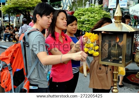 Bangkok, Thailand - December 16, 2011:  Thais lighting incense sticks from a brass lantern while carrying orange Marigold floral tributes at the Buddhist Erawan Shrine - stock photo