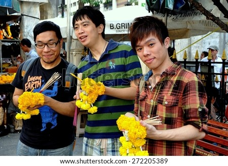 Bangkok, Thailand - December 16, 2011:  Three young Thai men with incense sticks and orange Marigold floral tributes at the Erawan Shrine - stock photo