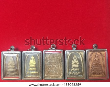 Bangkok, Thailand - famous amulet market with stone and metal Buddhist talismans bringing luck and good fortune on red background. background with copy space. - stock photo