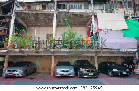 BANGKOK, THAILAND - 8 FEB 2016: Cars Parked beneath an Old, but Unfinished Building in Bangkok - stock photo
