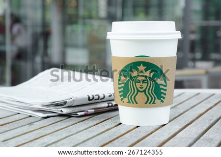 Bangkok, Thailand - Feb 26, 2015 : Starbucks take away coffee cup on the table, Starbucks brand is one of the most world famous coffeehouse chains from USA. - stock photo