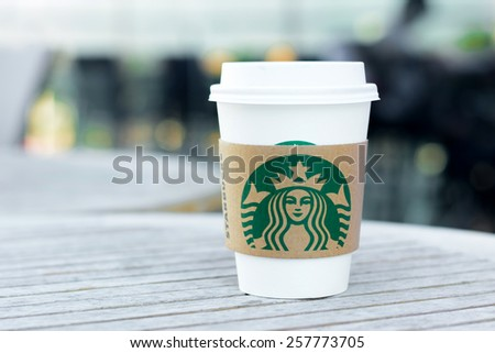 Bangkok, Thailand - Feb 26, 2015 : Starbucks take away coffee cup with logo on sleeve, Starbucks brand is one of the most world famous coffeehouse chains from USA. - stock photo