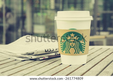 Bangkok, Thailand - Feb 26, 2015 : Starbucks take away coffee cup with newspaper on the table, Starbucks brand is one of the most world famous coffeehouse chains from USA - vintage tone image - stock photo