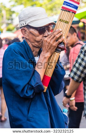 BANGKOK, THAILAND - FEBRUARY 22: An unidentified street musician performs at Chatuchak market on February 22, 2015 in Bangkok, Thailand. - stock photo