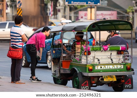 BANGKOK,THAILAND-FEBRUARY 9 2015: Chinese tourists ask TukTuk driver a question. TukTuk is a famous attraction in Bangkok. - stock photo
