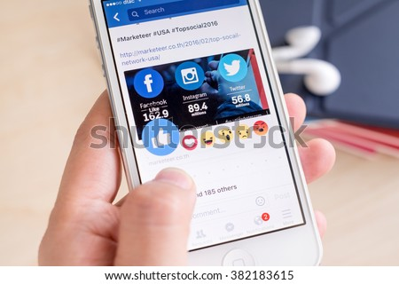 Bangkok, Thailand - February 26, 2016: Hand holding iPhone with New facebook like button (6 emoji) on screen ,Social media are using for information sharing and networking. - stock photo