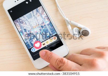 Bangkok, Thailand - February 26, 2016: Hand holding iPhone with New facebook like button (6 emoji) on screen ,Social media are using for information sharing and networking - stock photo