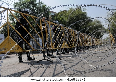 Bangkok, Thailand - February 11, 2011: Riot police stand guard behind razor wire at Government House during a nationalist Yellow Shirt rally. Protesters gathered in opposition to upcoming elections. - stock photo