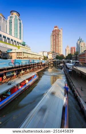 Bangkok, Thailand - February 8, 2015: Skyscraper and boat pier in Bangkok; water transportation by  speed boat is one of the alternative choice for solving the traffic congestion problem in Bangkok.