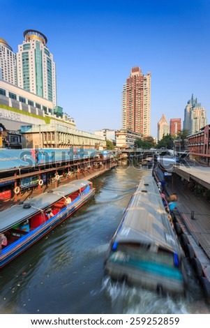 Bangkok, Thailand-February 8, 2015: Skyscraper and boat pier in Bangkok; water transportation by  speed boat is one of the alternative choice for solving the traffic congestion problem in Bangkok