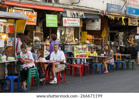 BANGKOK, THAILAND, February 16, 2015: Some customers are sitting at the restaurant tables in the Sukhumvit Soi 38, famous place of street food in the Thong Lor district in Bangkok, Thailand - stock photo