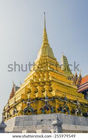 Bangkok, Thailand - Giants under golden pagoda in Royal Palace and Wat Phra Kaeo Complex - stock photo