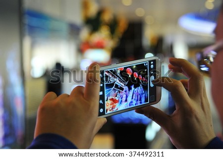 BANGKOK, THAILAND - JAN 18, 2014: A traveler uses a smartphone to capture a China themed interactive digital display at Don Muang International Airport. The airport is a hub for budget airlines. - stock photo