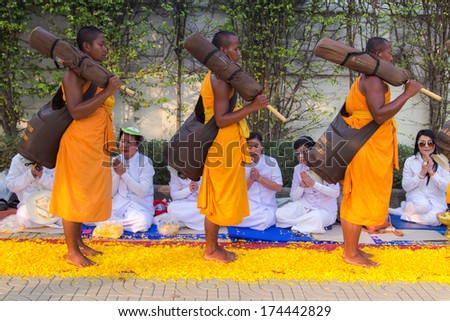 BANGKOK,THAILAND-JAN 27 : Row of Buddhist hike Thai monks on street strewn with marigold petals on the Thammachai hike establish the path of the great teachers on January 27, 2014 in Bangkok, Thailand