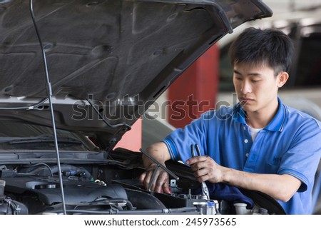 Bangkok, Thailand - January 21 : automobile mechanic examining car suspension of lifted  automobile at at Mitsubishi Motor Service station on January 21, 2015. Bangkok, Thailand.