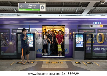Bangkok, Thailand - January 18, 2016:BTS skytrain full of people in train and one person waiting while calling on phone in waiting zone with sign of train destination on above at BTS Siam station - stock photo