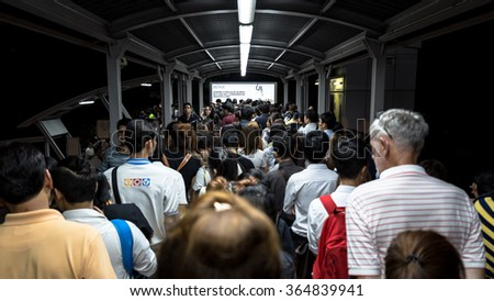 Bangkok, Thailand - January 18, 2016:Crowd of people walking out from BTS Mo Chit station to the road in rush hour at night. They have to walk cross a footbridge along with light and advertising board - stock photo