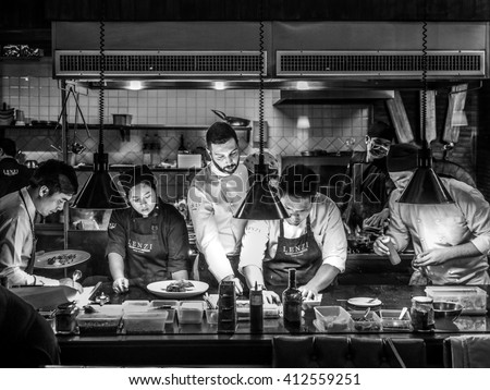 BANGKOK, THAILAND - January 16, 2016: Head chef coaches his team in a busy Italian Tuscan kitchen - stock photo
