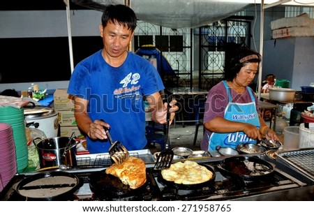 Bangkok, Thailand - January 17, 2012:  Husband and wife cooking food at their small restaurant at the MBK shopping complex outdoor food court - stock photo