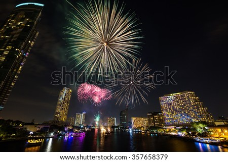 BANGKOK, THAILAND - 01 JANUARY 2016 - New year fireworks over the Chao Phraya river in front of various luxury hotels and condominiums along the waterfront, Bangkok, Thailand