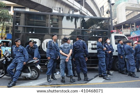 Bangkok, Thailand - January 9, 2011: Police officers gather by a van during a city centre Red Shirt rally. - stock photo