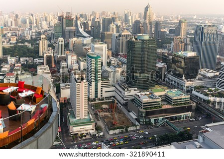 BANGKOK, THAILAND, JANUARY 14, 2015: Restaurant table with large view on the cityscape at the Red Sky Rooftop of the Centara hotel in Bangkok, Thailand. - stock photo