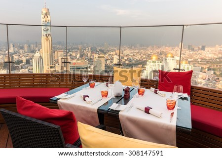 BANGKOK, THAILAND, JANUARY 14, 2015: Restaurant table with view on the Baiyoke tower and cityscape at the Red Sky Rooftop of the Centara hotel in Bangkok, Thailand. - stock photo