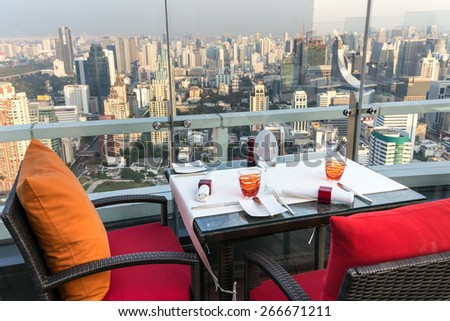BANGKOK, THAILAND, JANUARY 14, 2015: Restaurant table with view on the cityscape at the Red Sky Rooftop of the Centara hotel in Bangkok, Thailand. - stock photo