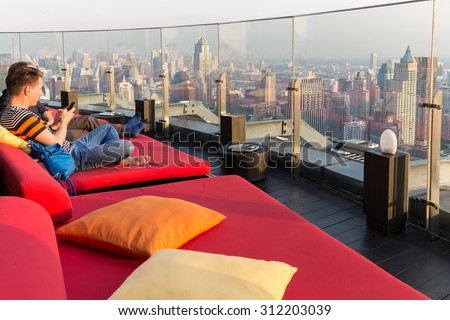 BANGKOK, THAILAND, JANUARY 14, 2015 : Restaurant table with view on the cityscape at the Red Sky Rooftop of the Centara hotel in Bangkok, Thailand. - stock photo