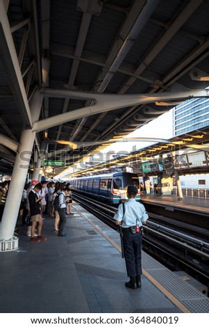 Bangkok, Thailand - January 18, 2016 : Security guard watching people while they waiting for the train to come to ensure safety of the passengers at BTS National Stadium station in the rush hour. - stock photo
