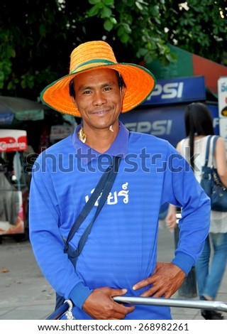 Bangkok, Thailand - January 16, 2011:  Smiling Thai man wearing an orange straw hat on Thanon Sathorn - stock photo