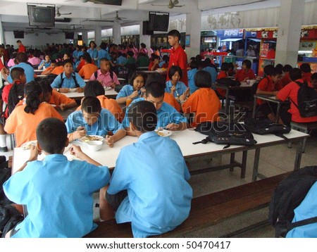BANGKOK, THAILAND - JANUARY 25 : Students sit for dinner in the canteen at Seekan school January 25 2006 in Bangkok. - stock photo