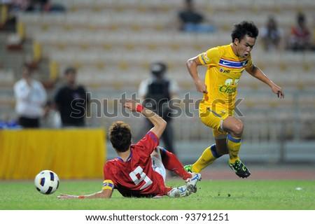 BANGKOK THAILAND-JANUARY 15:Sumanya Purisri (yellow) of Thailand in action during the 41st King's cup match between Thailand and Korea Rep at Rajamangala stadium on Jan15,2012 in Bangkok,Thailand. - stock photo