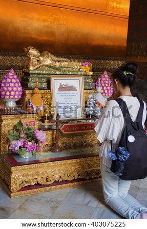 "BANGKOK, THAILAND - JANUARY 25th, 2013: Unknown young thai girl prays at the altar in a Buddhist temple ""Wat Pho"", which is the ""Temple of the Reclining Buddha"".  Bangkok Thailand. - stock photo"