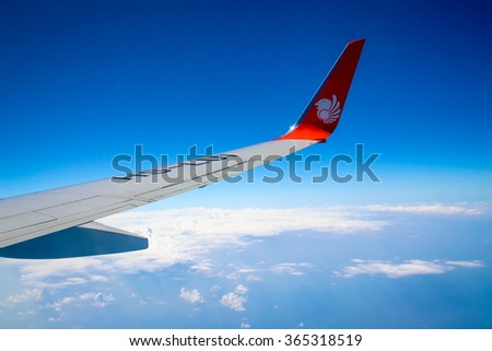 Bangkok, Thailand - JANUARY 1: Thai Lion air plane's wing with logo on the window with blue sky, the plane flying over Bangkok to Nakon si Thammarat on January 1 2016
