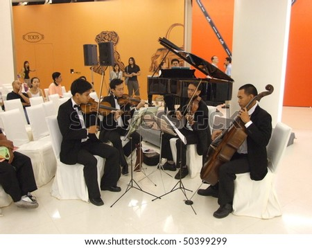 BANGKOK, THAILAND - JANUARY 8: Thai musicians play classical music at the Siam Paragon shopping center at the grand opening. January 8 2005, Siam center, Bangkok. - stock photo