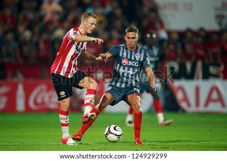 BANGKOK,THAILAND-JANUARY 8:TMario Gjurovski (R) of SCG Muangthong Utd. in action during The AIA Champions Cup match between SCG Muangthong Utd. and PSV at SCG Stadium on Jan8 ,2012 in ,Thailand. - stock photo