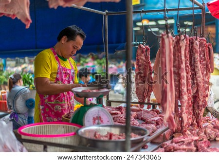 Bangkok, Thailand - January 25, 2015 Unidentified butcher man is selling raw pork on street in the morning at Houay Kwang area. - stock photo