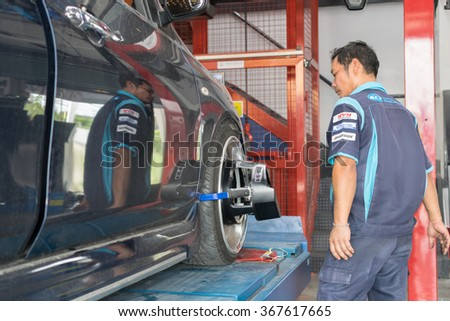 Bangkok, Thailand - January 16, 2016 : Unidentified serviceman checking suspension in a car at garage - stock photo