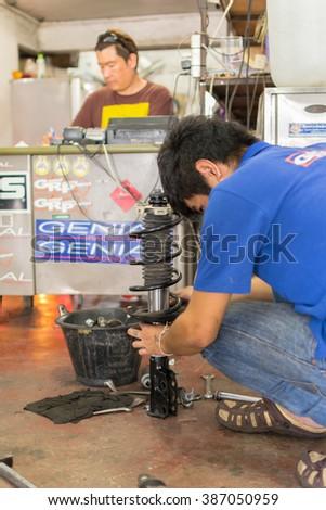 Bangkok, Thailand - January 22, 2016 : Unidentified serviceman checking suspension in a car at garage - stock photo
