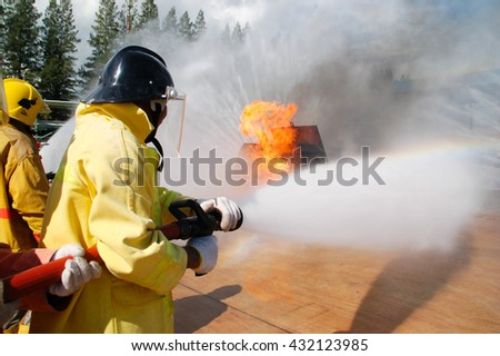 Bangkok, Thailand - July 19, 2006: Fireman demonstrating how to putting out a fire and use a fire extinguisher