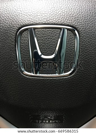 Bangkok, Thailand - July 1, 2017: Logo Honda and SRS Airbag on Black Steering Wheel. Honda is a Japanese multinational automotive manufacturing company.