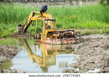 BANGKOK,THAILAND - JULY 21,2015 : The dirty backhoe working in mud lake in new bridge building site in Bangkok,Thailand
