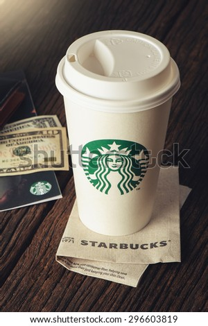 BANGKOK, THAILAND - JULY 15, 2015: White paper cup with Starbucks logo. Starbucks is the world's largest coffee house with over 20,000 stores in 61 countries. - stock photo