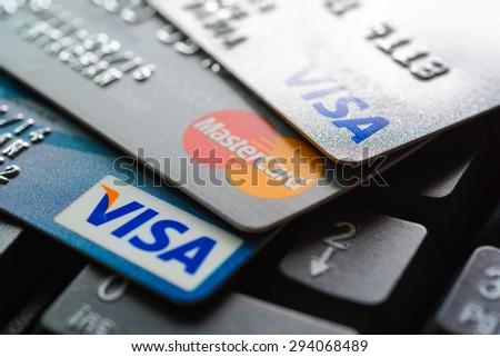 Bangkok, Thailand - Jun 23, 2015 : Group of credit cards on computer keyboard with VISA and MasterCard brand logos - stock photo