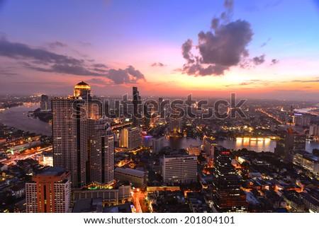 BANGKOK, THAILAND - JUNE 27 : Bangkok downtown at twilight time taken June 27, 2014 in Bangkok. Landmark of Bangkok riverside. This area is most luxury place on Chao Praya river bank. - stock photo
