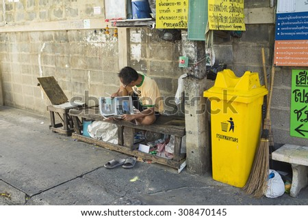 Bangkok, Thailand - June 29, 2015: Old man reading newspaper on old wooden bench, next to rubbish bin, on small alley in Bangkok - stock photo