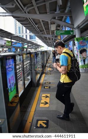 BANGKOK, THAILAND - JUNE 20, 2016: Traveller waits for BTS Skytrain at a city centre station in Bangkok Thailand. BTS rail public transport system serves 600,000 passengers daily. - stock photo